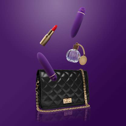 RIANNE S Classique Silicone Waterproof Bullet Vibrator shown next to a purse, lipstick, and bottle of perfume.